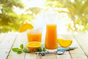 Glass and pitcher of orange juice on wooden, on green nature bac