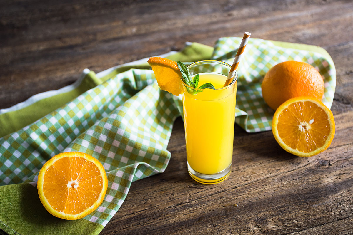 Orange juice in glass with mint, fresh fruits on wooden backgrou
